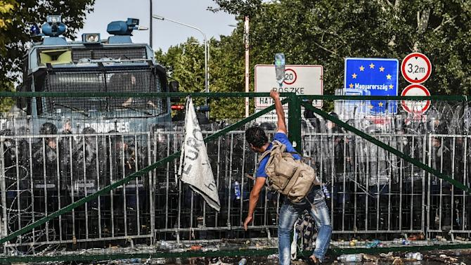 A refugee throws a bottle of water towards Hungarian riot police after they used water cannon to push back refugees at the Hungarian border with Serbia near the town of Horgos on September 16, 2015