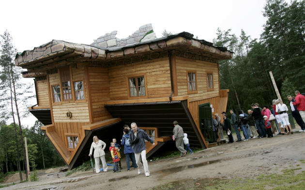 People wait in line to visit an upside-down house built at the Centre of Education and Promotion of the Region in the village of Szymbark