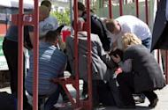 People try to help a woman injured by one of the blasts in the eastern Ukrainian city of Dnipropetrovsk, on April 27. President Viktor Yanukovych paid a visit to Ukraine's industrial heartland after the wave of blasts injured dozens of people