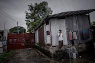 This picture taken on June 11, 2013 shows a refugee from Bangladesh using a mobile phone at a compound where asylum seekers in the Ping Che district of Hong Kong, near the border with mainland China. Hong Kong may be one of Asia's wealthiest hubs, but the picture is very different for hundreds of asylum seekers forced into slum-like conditions as they scrape a living in the city