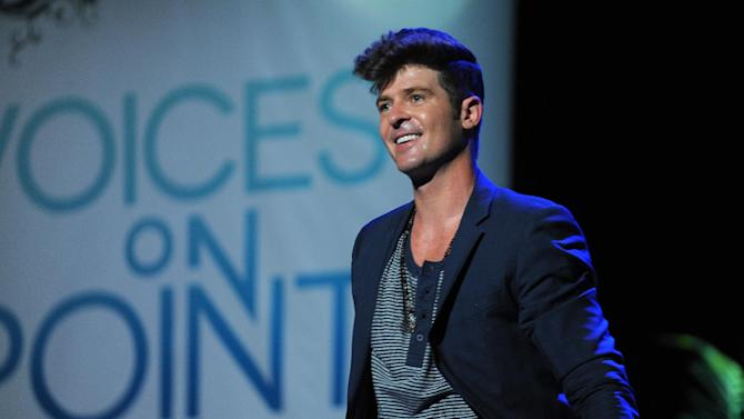 "FILE - In this Sept. 15, 2012 publicity photo provided by the Point Foundation, Robin Thicke performs at ""Voices On Point"" Concert & Gala held at The Wiltern theatre, in Los Angeles. Thicke originally didn't plan to release the unrated version of his music video for the song ""Blurred Lines,"" which features nude models prowling around him and rappers Pharrell and T.I. Thicke's unrated video hit the Web on Tuesday, March 26, 2013, and so far it has more than 700,000 views. (AP Photo/Point Foundation, Colin Young-Wolff, File)"