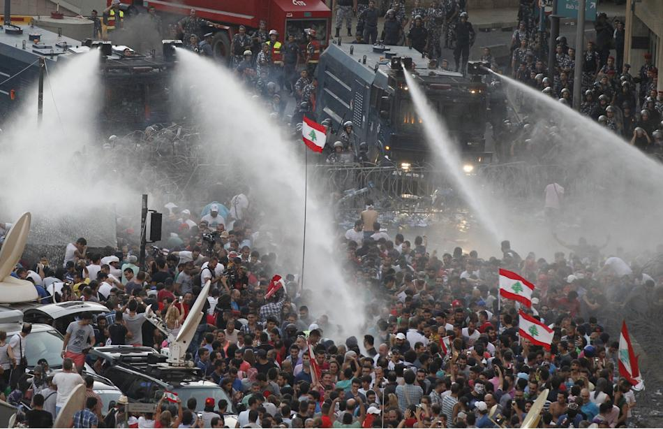 Lebanese protesters are sprayed with water during a protest against corruption and against the government's failure to resolve a crisis over rubbish disposal, near the government palace in Beirut,