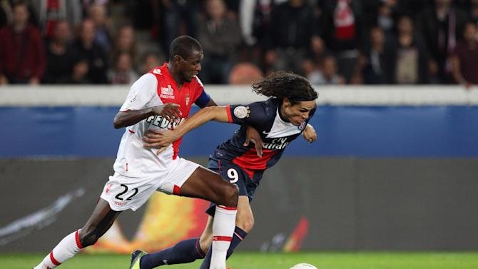 Paris Saint Germain's forward Edinson Cavani from Uruguay, right, challenges for the ball with Monaco's defender Eric Abidal, during their French League One soccer match, at the Parc des Princes stadium, in Paris, Sunday, Sept. 22, 2013