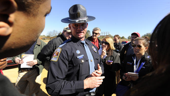 Alabama state trooper Kevin Cook, center, speaks to media, Saturday, Feb. 2, 2013, in Midland City, Ala. Authorities said they still have an open line of communication with an Alabama man accused of abducting a 5-year-old child and holding him hostage in a bunker since Tuesday, Jan. 29. Sheriff Wally Olson said Saturday that Jimmy Lee Dykes has told them that he has blankets and an electric heater in the bunker.  (AP Photo/al.com, Joe Songer) MAGS OUT.