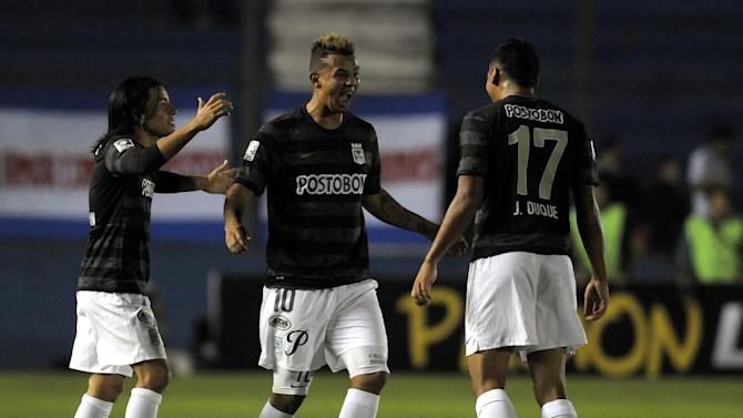 Edwin Cardona of Colombia's Atletico Nacional, center, celebrates with teammates Jefferson Duque, right, and  Sherman Cardenas, after scoring a goal during a Copa Libertadores soccer game against Uruguay's Nacional in Montevideo, Uruguay, Tuesday, March 18, 2014