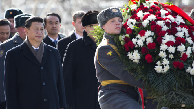 Chinese President Xi Jinping, left, attends a wreath laying ceremony at the Tomb of Unknown Soldier in Moscow, Russia, Friday, March 22, 2013. Russia is Xi Jinping's first foreign destination as China's president. Xi's talks with Putin on Friday are set to focus on oil and gas as China seeks to secure new energy resources to fuel its growing economy. (AP Photo/Misha Japaridze)