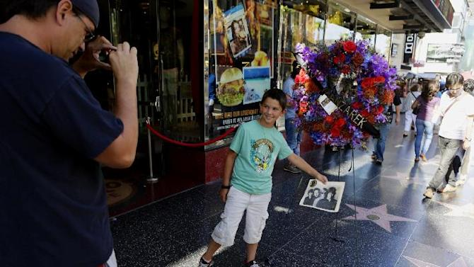 Darron Quigley,left, takes a photo of his son Jack Quigley, 8, from Simi Valley, Calif., in front of flowers placed on the Hollywood Walk of Fame star of Ray Manzarek of The Doors today, Monday, May 20, 2013, in Los Angeles Monday, May 20, 2013. Ray Manzarek, the keyboardist and founding member of The Doors who had a dramatic impact on rock 'n' roll, has died. He was 74. (AP Photo/Damian Dovarganes)