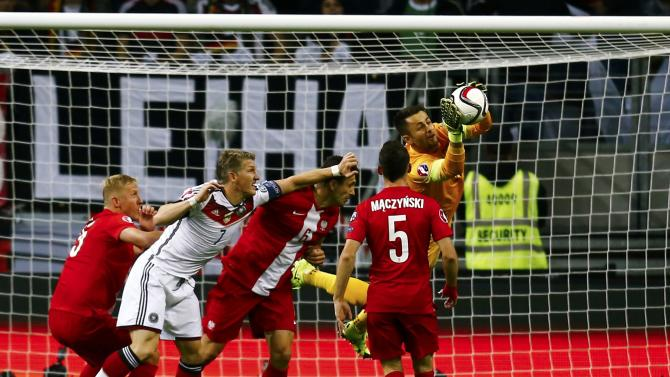 Germany's Schweinsteiger attacks Poland's goalkeeper Fabianski during their Euro 2016 qualification match in Frankfurt