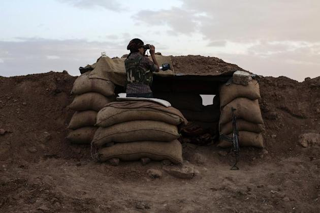 A fighter of the Committees for the Protection of the Kurdish People looks through binoculars behind sand bags on October 19, 2013 in Derik, in the northeastern Hasakeh governorate on the border with Turkey and Iraq