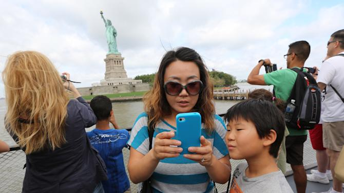 Visitors to fhe Statue of Liberty take photos as they arrive on the first tourist ferry to leave Manhattan, Thursday, July 4, 2013, in New York. The Statue of Liberty finally reopened on the Fourth of July months after Superstorm Sandy swamped its little island in New York Harbor as Americans across the country marked the holiday with fireworks and barbecues. (AP Photo/Mary Altaffer)