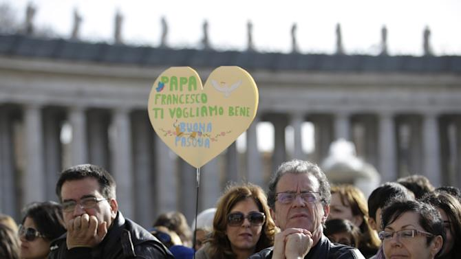 """Faithful hold a heart shaped banner reading in Italian """"Pope Francis we love you. Happy Easter"""" in St. Peter's square at the Vatican on the occasion of the celebration of the Easter mass Sunday, March 31, 2013. """"Our daily problems and worries can wrap us up in ourselves, in sadness and bitterness, and that is where death is,"""" he said. """"Let the risen Jesus enter your life, welcome him as a friend, with trust: he is life!"""" said Pope Francis during the Easter vigil. (AP Photo/Andrew Medichini)"""