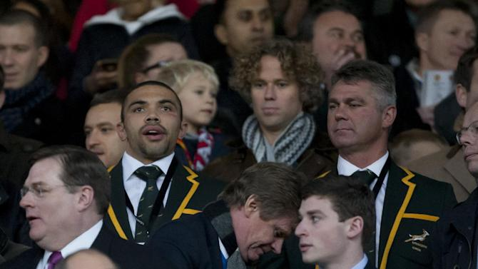 South African Rugby Union player Bryan Habana, centre left, and coach Heyneke Meyer, centre right,  takes their seats in the stands before Manchester United's English Premier League soccer match against Arsenal at Old Trafford Stadium, Manchester, England, Saturday Nov. 10, 2013