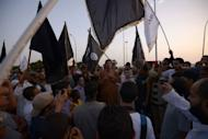 Supporters and members of hardline Islamist group of Ansar al-Sharia shout slogans as they wave Al-Qaeda affiliated flags during a demonstration against a film mocking Islam in Benghazi
