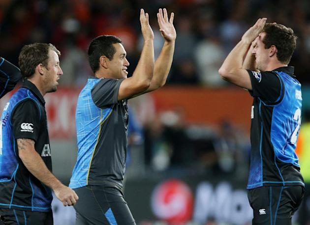 New Zealand's Matt Henry, right, celebrates with teammates Luke Ronchi, left, and Ross Taylor following their four wicket on over South Africa in their Cricket World Cup semifinal in Auckland, New
