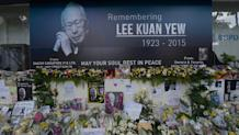 Pictures and flowers are seen in front of a memorial area for Singapore's late former prime minister Lee Kuan Yew outside the parliament building where he lies in state in Singapore, March 28, 2015