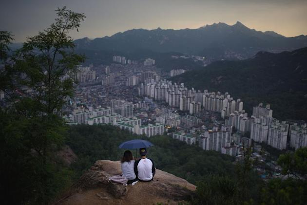 A couple shelter beneath an umbrella on a hilltop overlooking skyline of northern Seoul, on June 11, 2015
