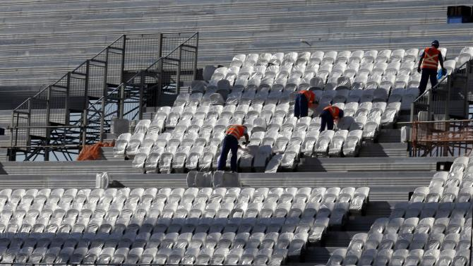 Labourers work on the construction of the Arena de Sao Paulo Stadium in Sao Paulo