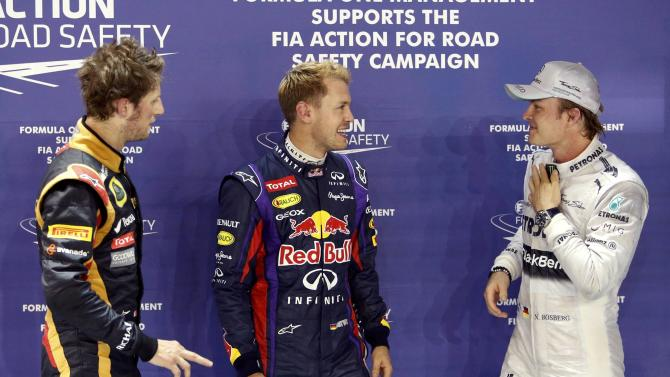 Lotus F1 Formula One driver Grosjean, Red Bull Formula One driver Vettel and Mercedes Formula One driver Rosberg stand together after the qualifying session of the Singapore F1 Grand Prix in Singapore