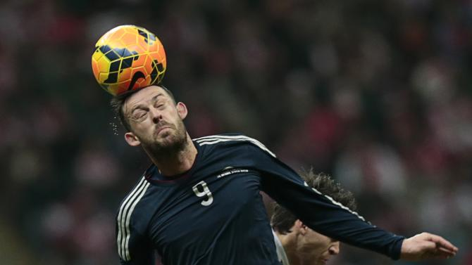 Steven Fletcher of Scotland jumps for the ball during international friendly soccer match against Poland in Warsaw