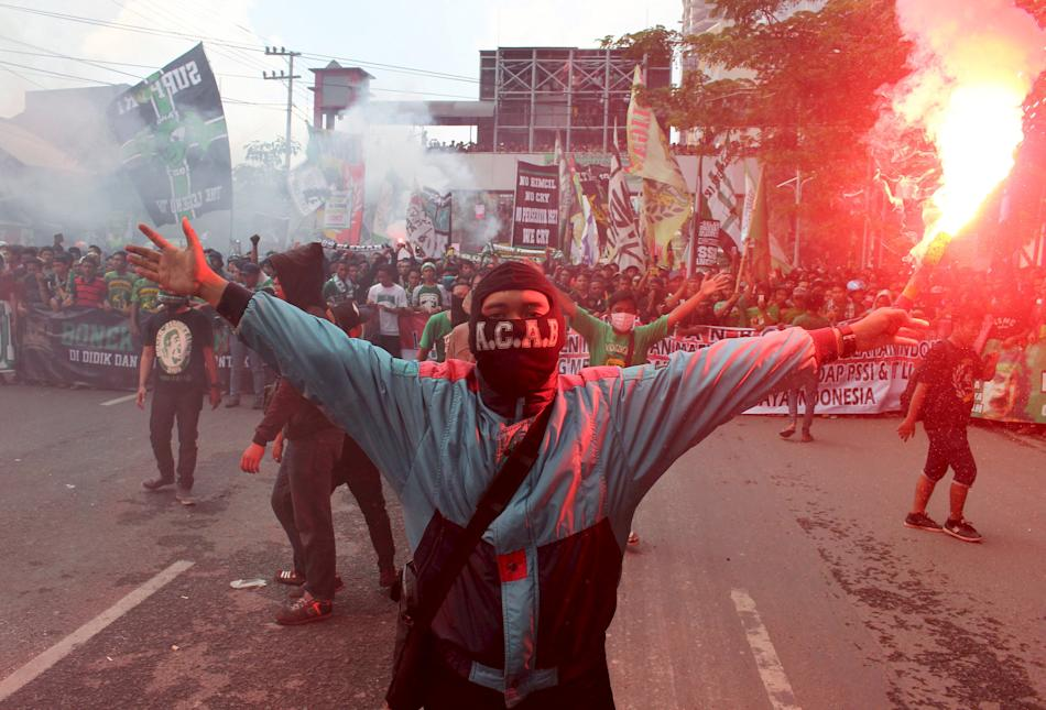 A supporter of Surabaya 1927 soccer club holds a flare during a protest against local soccer association PSSI Extraordinary Congress in Surabaya