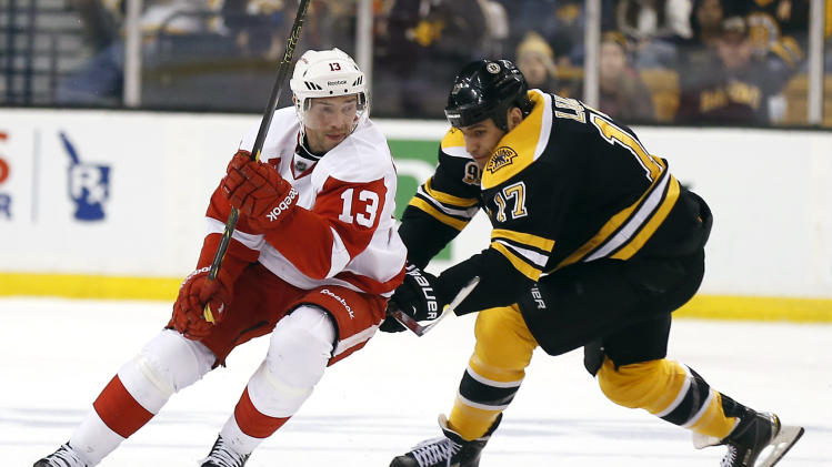 Detroit Red Wings' Pavel Datsyuk (13) tries to get around Boston Bruins' Milan Lucic (17) during the second period of Game 2 of a first-round NHL hockey playoff series in Boston, Sunday, April 20, 2014