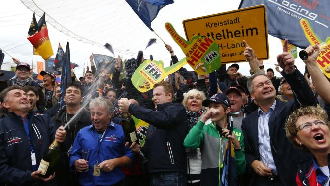 Supporters of Germany's Red Bull Formula One driver Vettel celebrate during public viewing session of the Formula One Grand Prix of India in Heppenheim