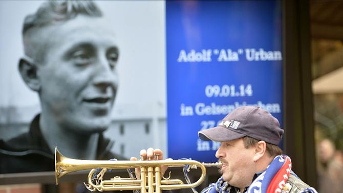 A Schalke fan plays a trumpet in front of a picture of Adolf Urban, a storied player for soccer club FC Schalke 04 who was killed in Eastern Front fighting in World War II and  and who is being reburied in a cemetery in Gelsenkirchen, Germany, Wednesday, Nov. 20, 2013. Urban helped Schalke win five German championships and one German cup before he died 1943  in Russia. His body returned home after 70 years now to a cemetery overlooking the Schalke stadium