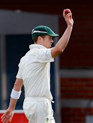 Australia's paceman Peter Siddle raises the ball after taking five Sri Lankan wickets on the third day of their first cricket Test match in Hobart, on December 16, 2012