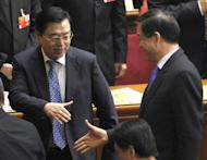 """File photo shows Bo Xilai (R), former leader of the Chinese megacity of Chongqing, shaking hands with Zhang Dejiang, Chongqing's new party head, on March 13. The public demise of Bo had brought """"great damage"""" to the country and the ruling Communist Party, Zhang said on Monday"""
