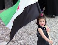 A handout picture released by the Shaam News Network purportedly shows a Syrian girl carrying the old national flag, adopted by the opposition, during an anti-regime demonstration in Daraa on April 22. United Nations ceasefire monitors were touring towns near the Syrian capital, an official said, as the European Union slapped new sanctions on the regime of Bashar al-Assad