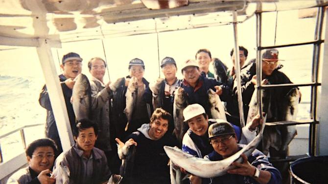 """This 2002 photo provided by Cubby's BBQ owner Bobby Egan shows Egan, center, with a group of North Koreans displaying their catches during a fishing trip with off Long Island, N.Y Egan had a well-documented, decades-long friendship with North Korean diplomats posted to the United Nations in New York. His book about his experiences dealing with the North Koreans, called """"Eating with the Enemy,"""" was optioned by HBO, and actor James Gandolfini was set to portray Egan in the film before his untimely death last month. (AP Photo/Courtesy Bobby Egan)"""