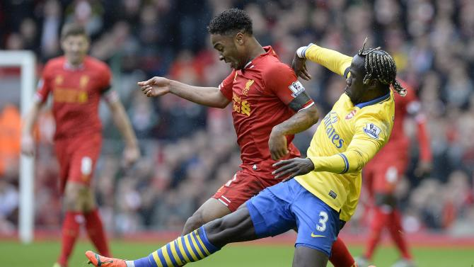 Liverpool's Sterling challenged by Arsenal's Sagna during their English Premier League match at Anfield Stadium in Liverpool