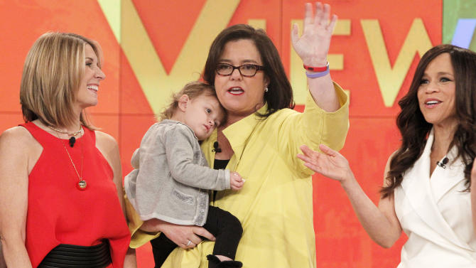 "In this image released by ABC, co-hosts Nicolle Wallace, left, Rosie O'Donnell, holding daughter Dakota, center and Rosie Perez appear on the set of ""The View,"" on Thursday, Feb. 12, 2015 in New York. O'Donnell has ended her second stint on ""The View,"" her goodbye about as short as her tenure. Holding her toddler daughter, she made her exit Thursday, Feb. 12, in a brief segment. She thanked the show's creator, Barbara Walters, and promised to bring her glue gun back someday for a crafting segment. She had returned to ""The View"" in September, part of a revamp aimed at stopping a ratings slide, joining Whoopi Goldberg, Perez and Wallace on the panel. (AP Photo/ABC, Lou Rocco)"