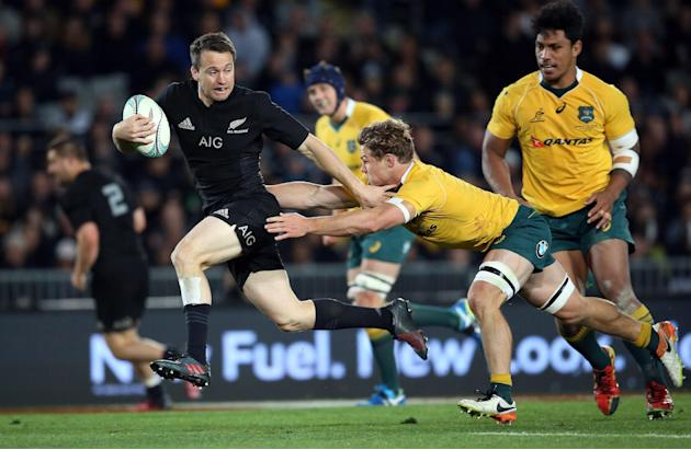 New Zealand's Ben Smith (L) breaks a tackle from Australia's Michael Hooper during the third rugby Bledisloe Cup at Eden Park in Auckland on October 22, 2016