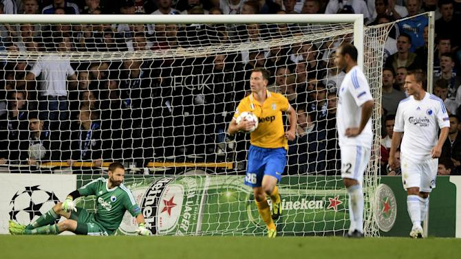 Juventus' Stephan Lichtsteiner , centre right, returns the ball after his teammate Fabio Quagliarella scored the equalizing goal , with FC Copenhagen's goalkeeper Johan Wiland of Sweden, left, during their Champions League Group B soccer match at Parken Stadium, Copenhagen, Denmark, Tuesday Sep. 17, 2013