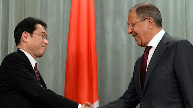 Russian Foreign Minister Sergei Lavrov (R) shakes hands with his Japanese counterpart Fumio Kishida after a joint press conference following their meeting in Moscow on September 21, 2015