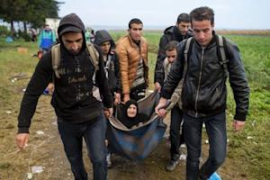 Migrants carry an elderly woman as they walk on a field, after they crossed the border with Serbia, near Tovarnik, Croatia