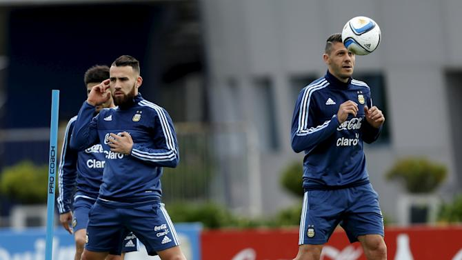 Argentina's Demichelis eyes the ball next to Otamendi during a training session in Buenos Aires