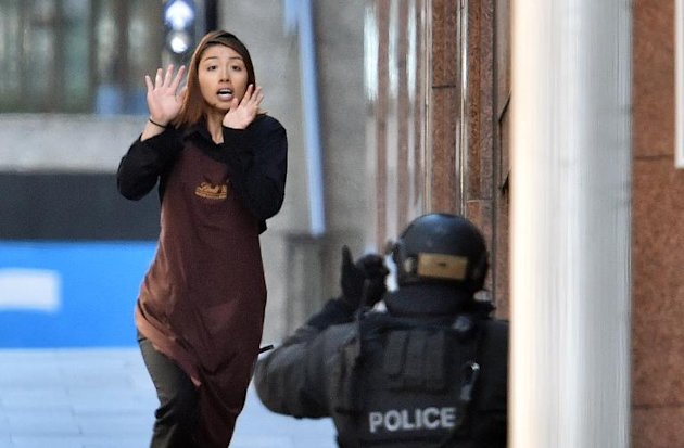 A hostage who escaped runs towards police from a cafe in the central business district of Sydney on December 15, 2014