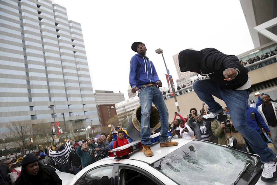 Protesters jump on a police car at a rally to protest the death of Freddie Gray who died following an arrest in Baltimore