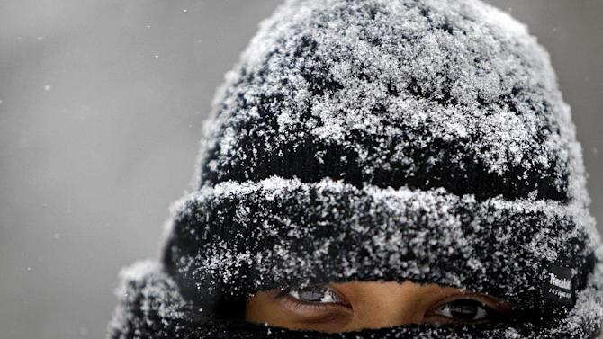 Jackie Arrandondo, 19,  is  covered with snow as she waits for the city bus, Friday, Feb.  22, 2013 in Minneapolis.  A major snowstorm that buried parts of the Midwest grazed southern Minnesota, where two to three inches of snow snarled the morning commute in the Twin Cities area. (AP Photo/The Star Tribune, Elizabeth Flores)  MANDATORY CREDIT; ST. PAUL PIONEER PRESS OUT; MAGS OUT; TWIN CITIES TV OUT