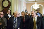 Majority Leader Harry Reid (C) is flanked by Sen. Ben Cardin (L) and Sen. Dick Durbin (R) as they leave a caucus meeting and head toward the Senate floor in Washington on December 28, 2012. With the clock ticking toward a New Year's time bomb of huge tax increases and spending cuts, US lawmakers worked feverishly Saturday to keep America from tumbling off the so-called fiscal cliff.