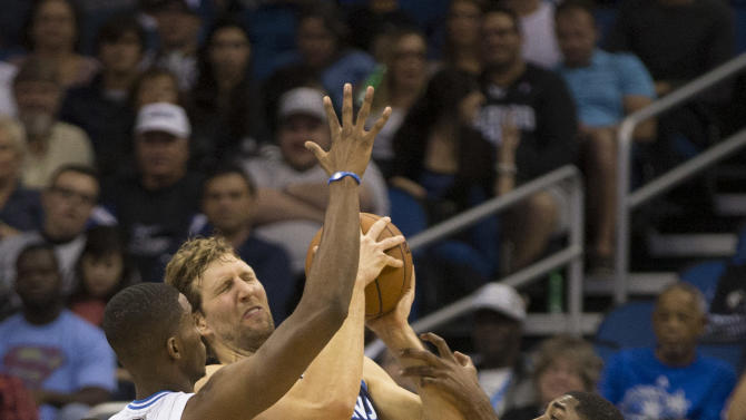 Orlando Magic's Maurice Harkless and E'Twaun Moore (55) cover and foul Dallas Mavericks' Dirk Nowitzki, center, during the first half of an NBA basketball game in Orlando, Fla., Saturday, Nov. 16, 2013