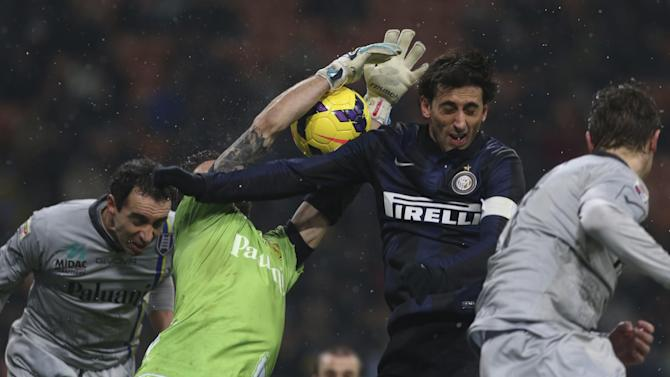 Chievo goalie Christian Puggioni, second left, saves on a header of Inter Milan Argentine forward Diego Milito during a Serie A soccer match between Inter Milan and Chievo Verona, at the San Siro stadium in Milan, Italy, Monday, Jan.13, 2014
