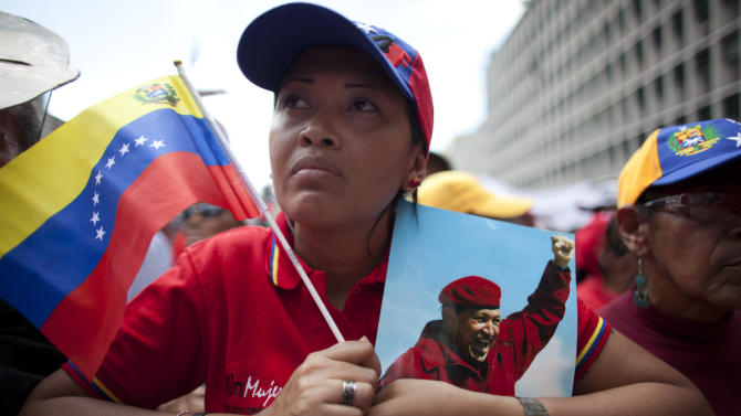 "A woman holds a picture of Venezuela's President Hugo Chavez and the country's national flag during an event commemorating the violent street protests of 1989 known as the ""Caracazo,""  in Caracas, Venezuela, Wednesday, Feb. 27, 2013. The wave of the 1989 violent protests, seen by the Chavez government as a ""popular uprising,"" was in response to the economic measures imposed by then President Carlos Andres Perez.  (AP Photo/Ariana Cubillos)"