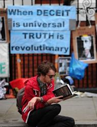 A man reads a book outside the Ecuadorian embassy in London, on June 22, 2012, where Wikileaks founder Julian Assange is seeking political asylum. Assange has said he chose Ecuador's embassy instead of his home country's because he felt Australia had done nothing to protect him, a charge the government has denied.