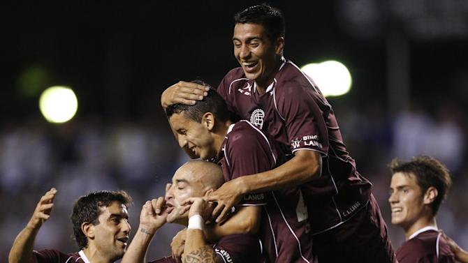 Santiago Silva, second from left, of Argentina's Lanus, celebrates with teammates after scoring against Paraguay's Libertad at a Copa Sudamericana soccer game in Asuncion, Paraguay, Thursday, Nov. 21, 2013
