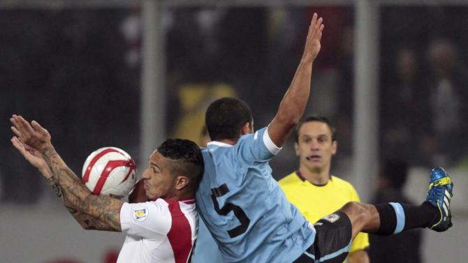 Peru's Paolo Guerrero is challenged by Uruguay's Walter Gargano for the ball during their 2014 World Cup qualifying soccer match in Lima