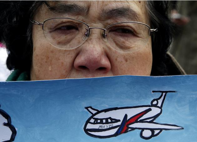 Wang Guohui, mother of Li Zhi, a passenger of the missing flight MH370, cries at a gathering in Beijing