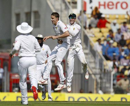 South Africa's Morkel and de Villiers celebrate after Morkel took the wicket of India's captain Kohli on the first day of their third test cricket match in Nagpur